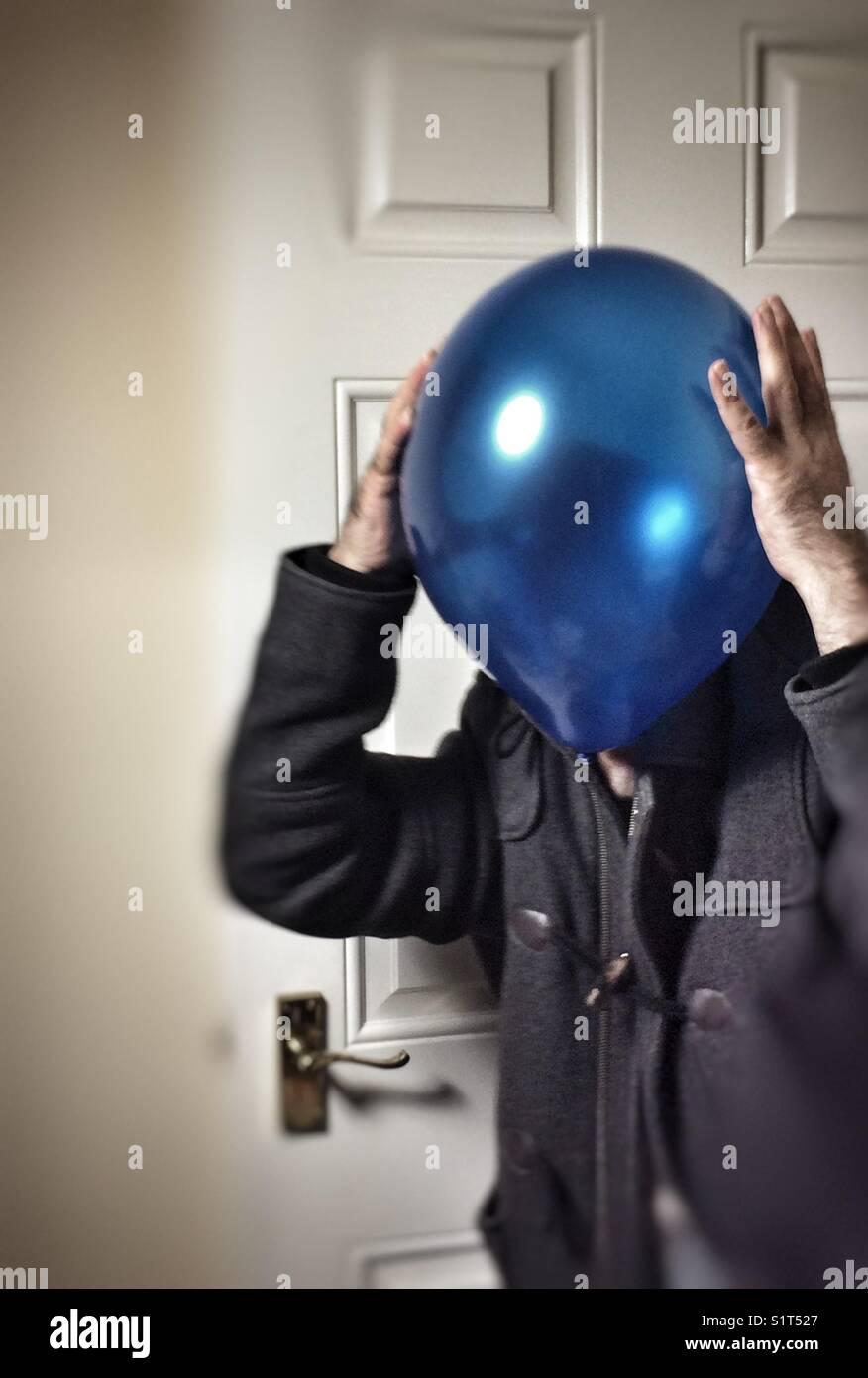 Mr Blue/baloon headache walking into the room - Stock Image
