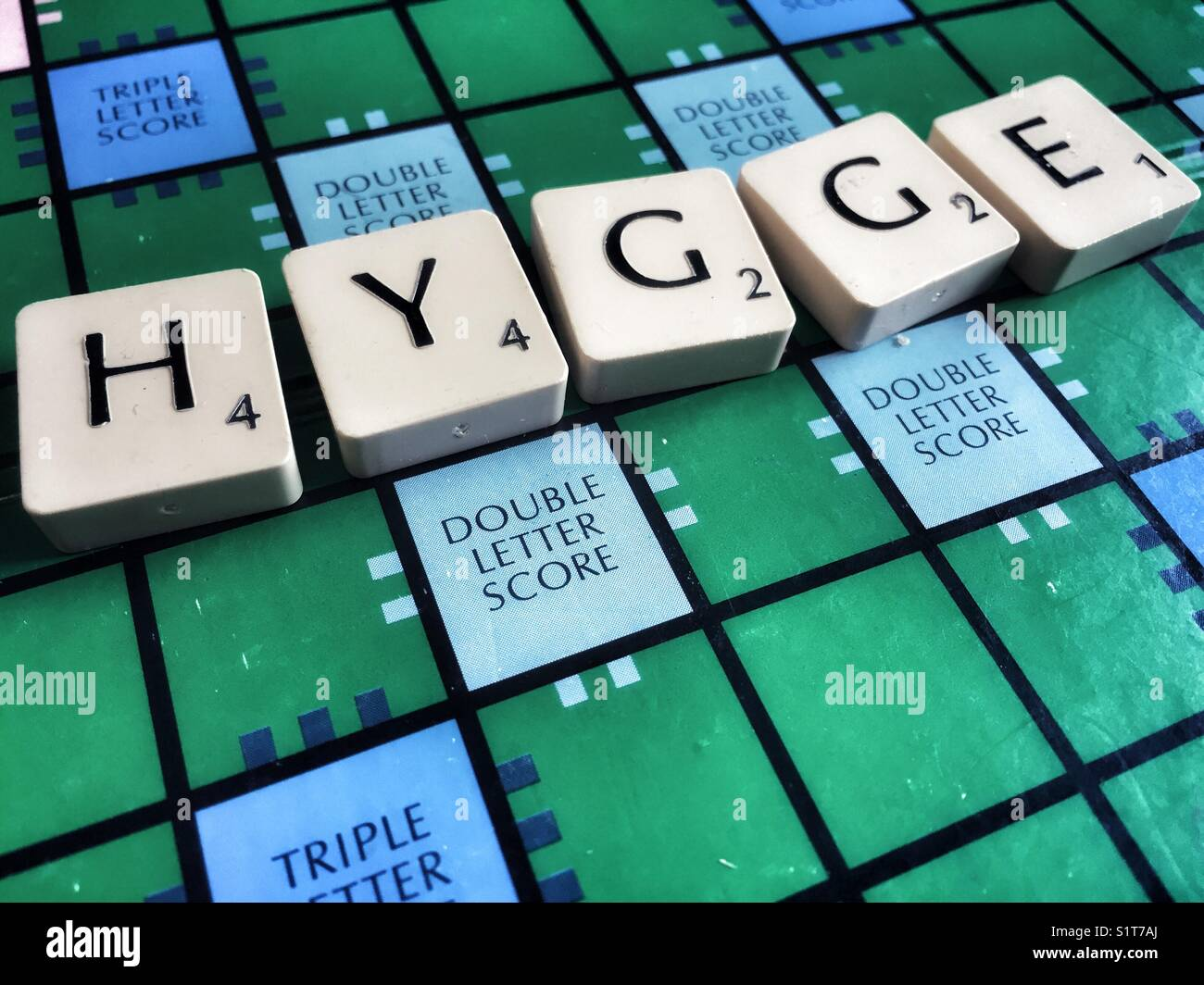 The Danish word hygge written on a scrabble board - Stock Image