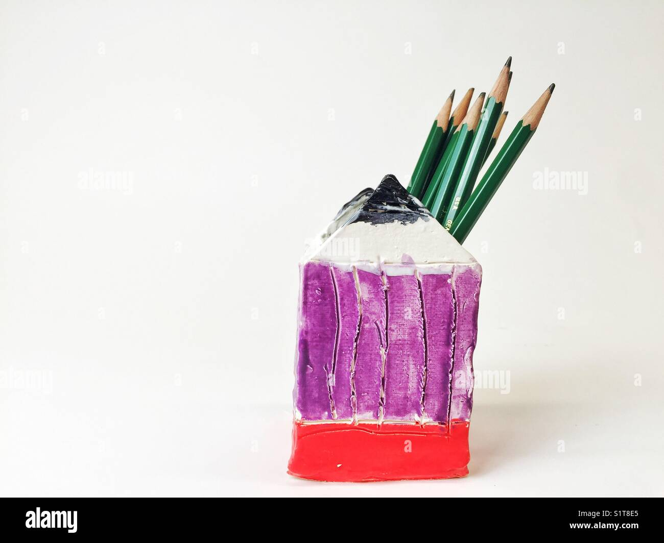 Pencils in pencil shaped ceramic container on white background - Stock Image