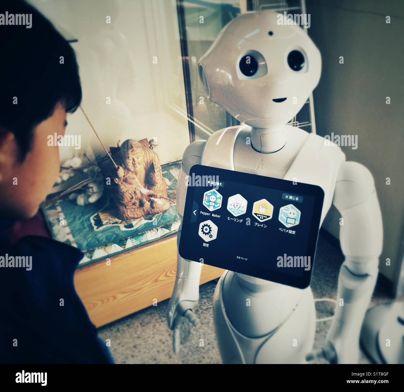 Asian 6 years old boy looking at control panel of interactive robot in Japan - Stock Image