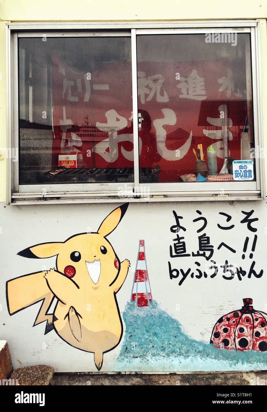 Fast food window with Pikachu  character and Kusama's pumpkin painted on the wall. Naoshima island, Japan - Stock Image