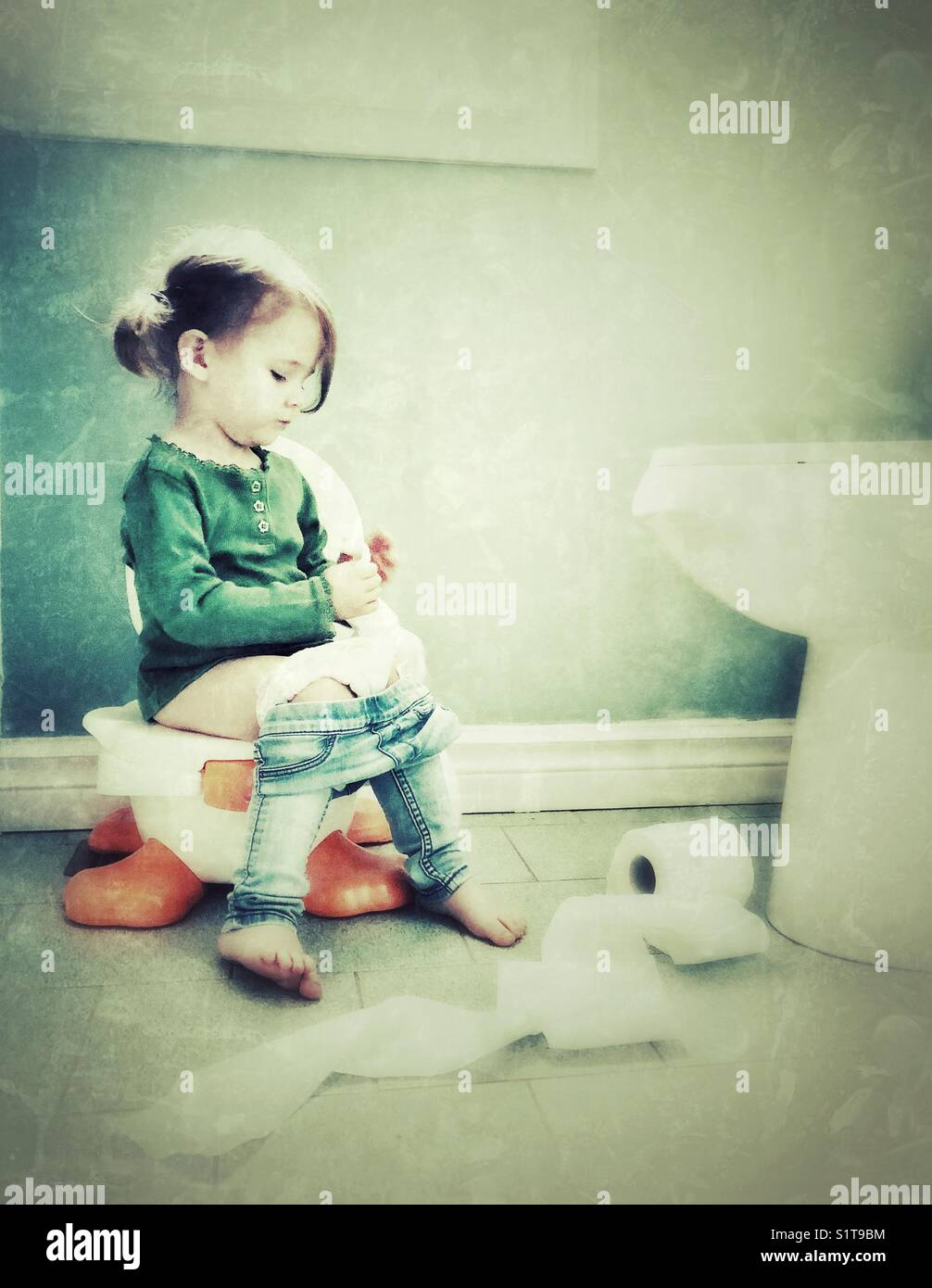 Toddler girl playing with toilet paper while potty training - Stock Image
