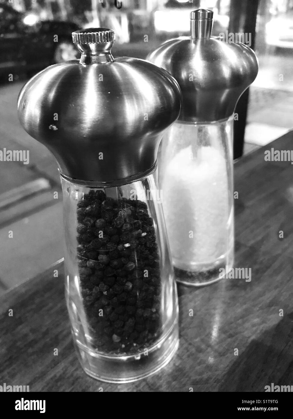 Salt and pepper mills in a restaurant window - Stock Image