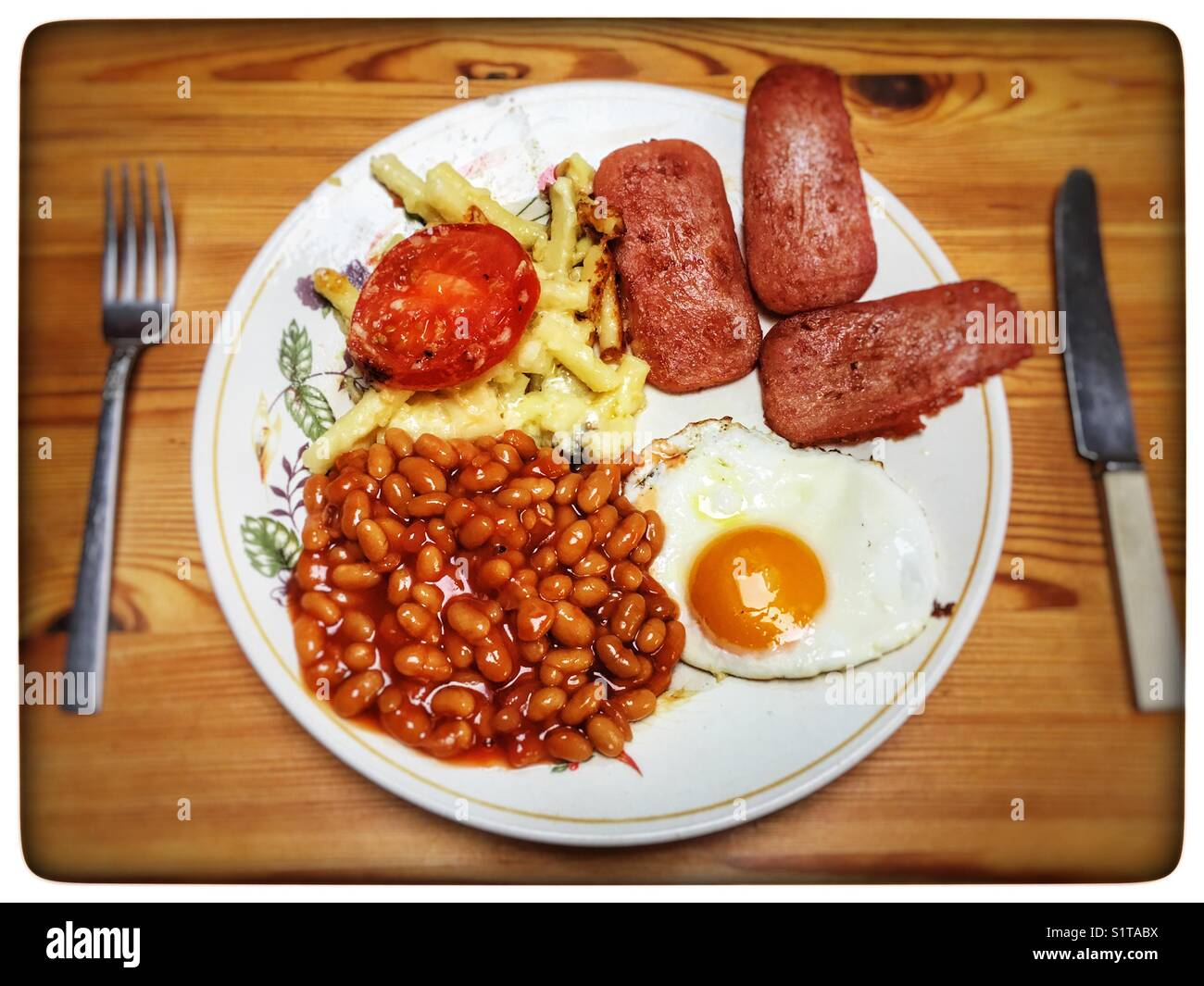 Spam fritters, macaroni cheese, fried egg and baked beans. - Stock Image