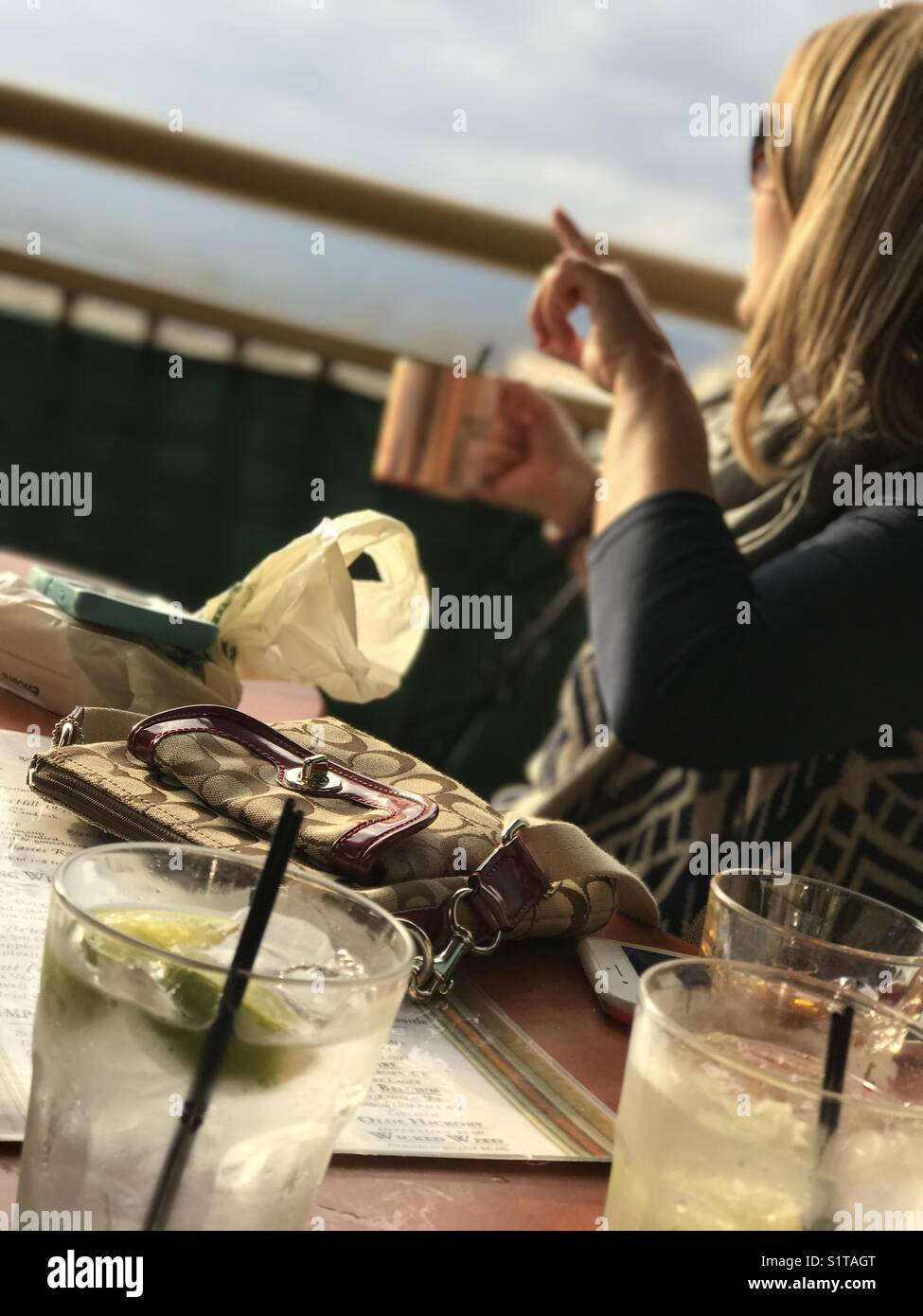 Woman Enjoying a Cocktail on a Balcony in Asheville, NC - Stock Image
