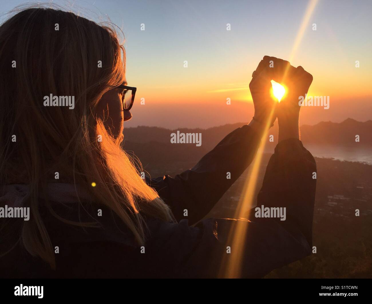 Grasping the sun at Mount Agung, Bali - Stock Image