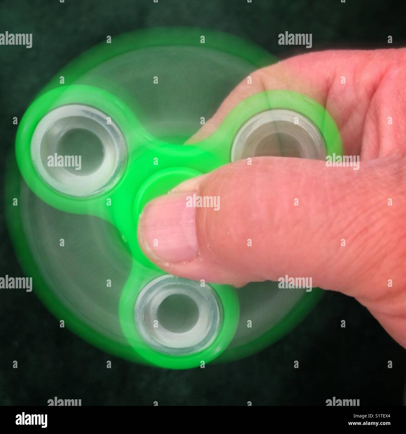 Green fidget spinner in action - Stock Image