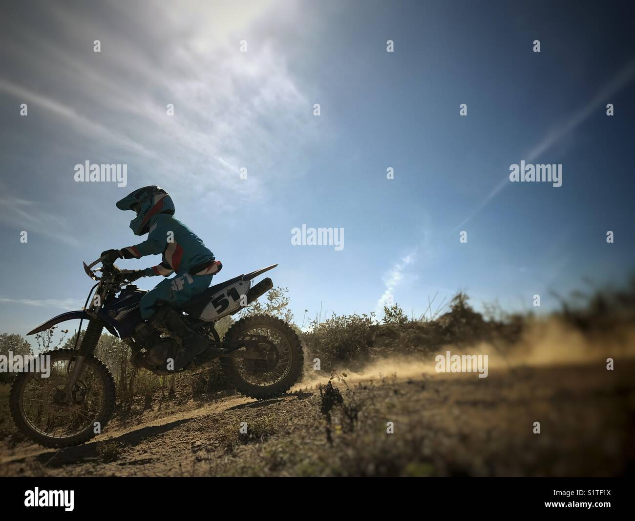 Boy riding a dirt bike in the summer sun. - Stock Image