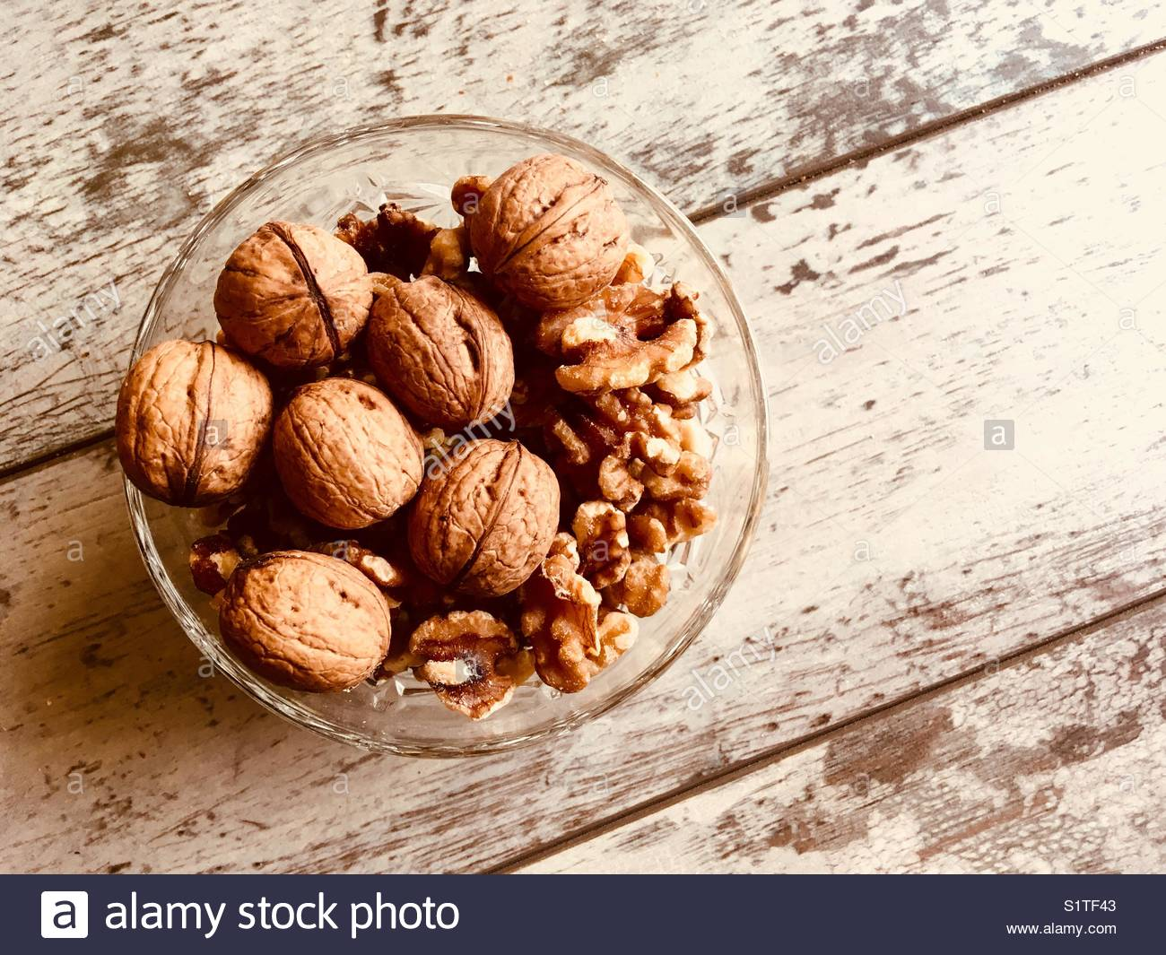 Walnuts presented in a glass bowl - copy space provided - Stock Image