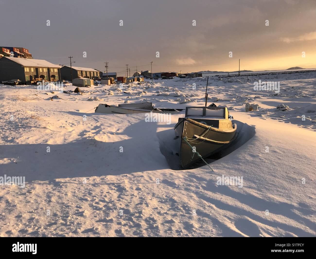 Boat buried in snow in Frobisher Bay in Iqaluit, Nunavut, Canada - Stock Image