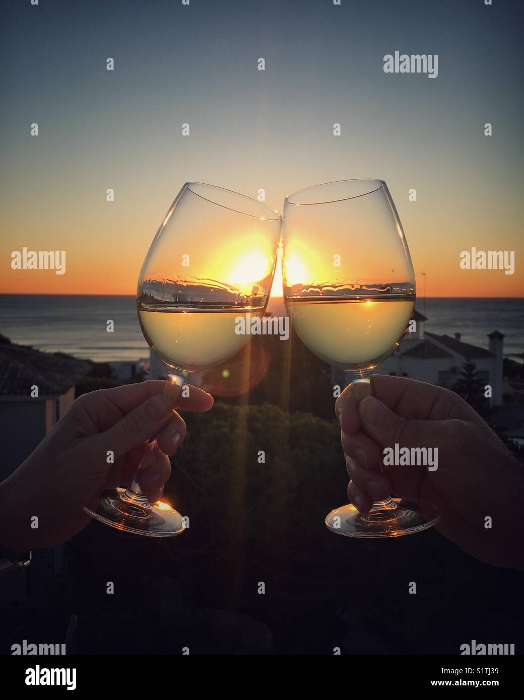 Two glasses clinking at sunset. Cheers! - Stock Image