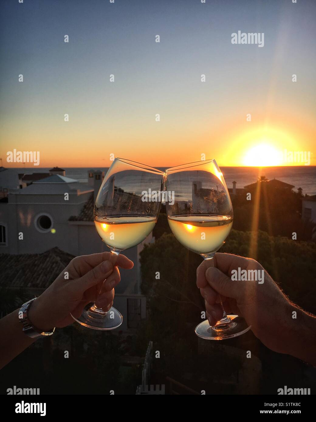 Two wine glasses clinking together at sunset. Cheers! - Stock Image
