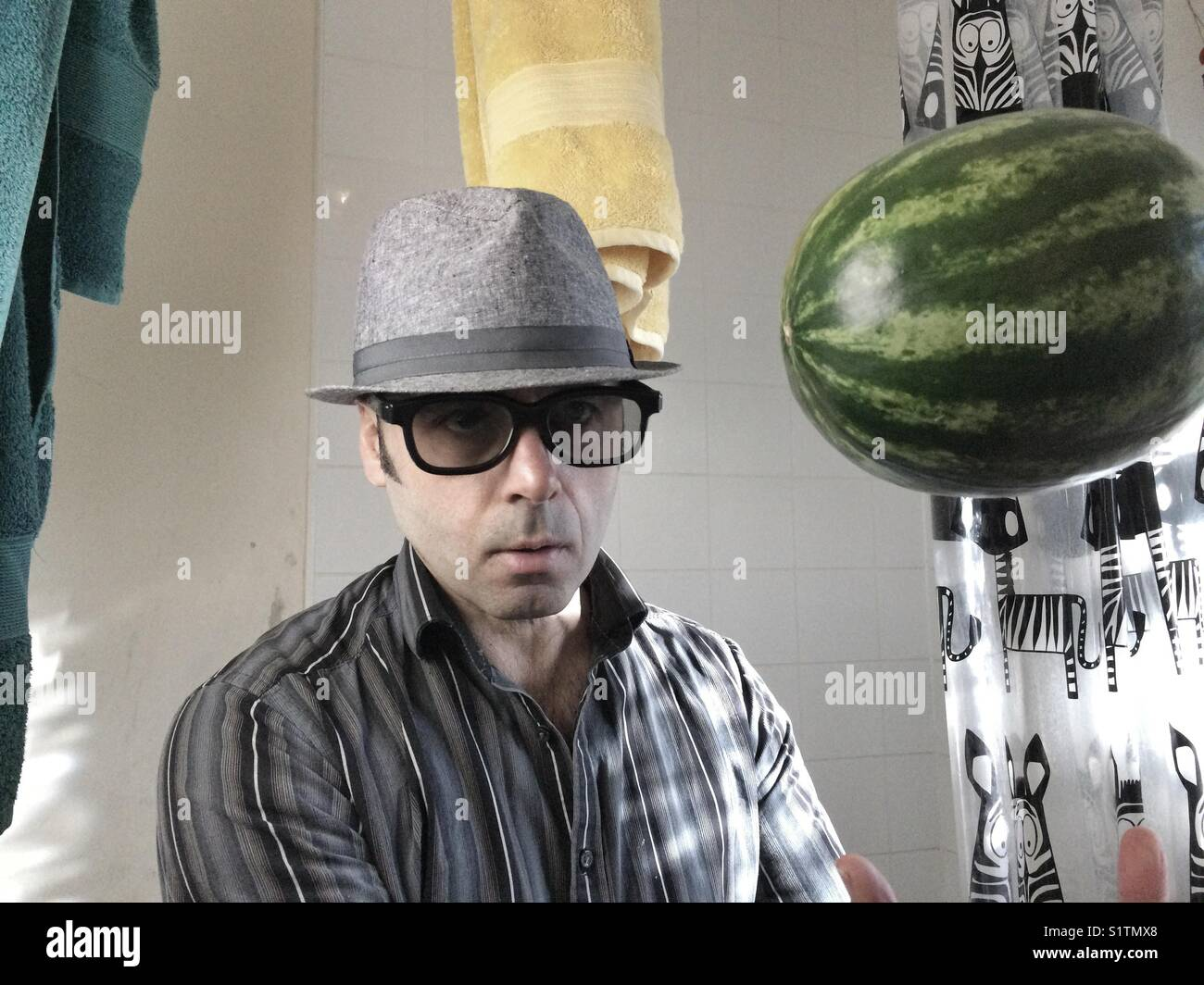 Portrait of man with dark glasses and hat in toilet with watermelon in the air - Stock Image