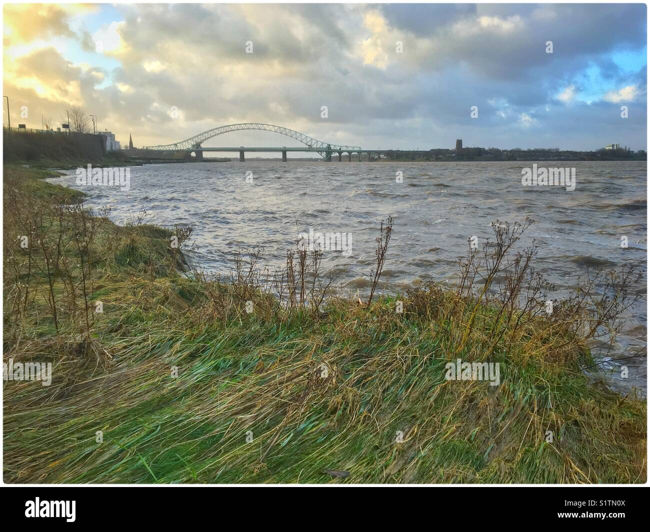 Standing on Wigg Island looking across the River Mersey at the old Runcorn Jubilee bridge - Stock Image