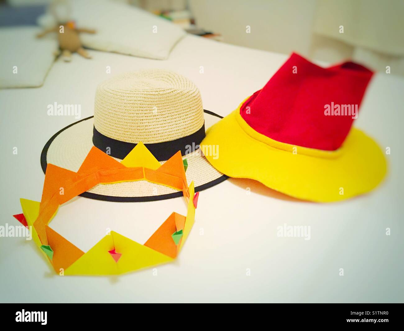 Paper origami yellow crown, red and yellow hat, white and black wide hat. - Stock Image