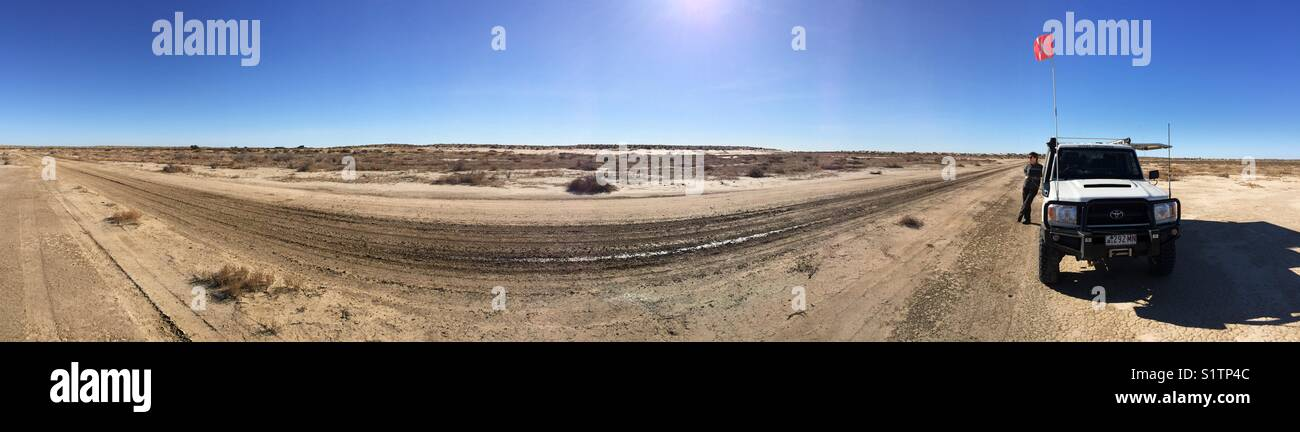180 degrees panorama showing a four wheel drive and sand flag with blue sky and a sun flare in the Australian desert - Stock Image