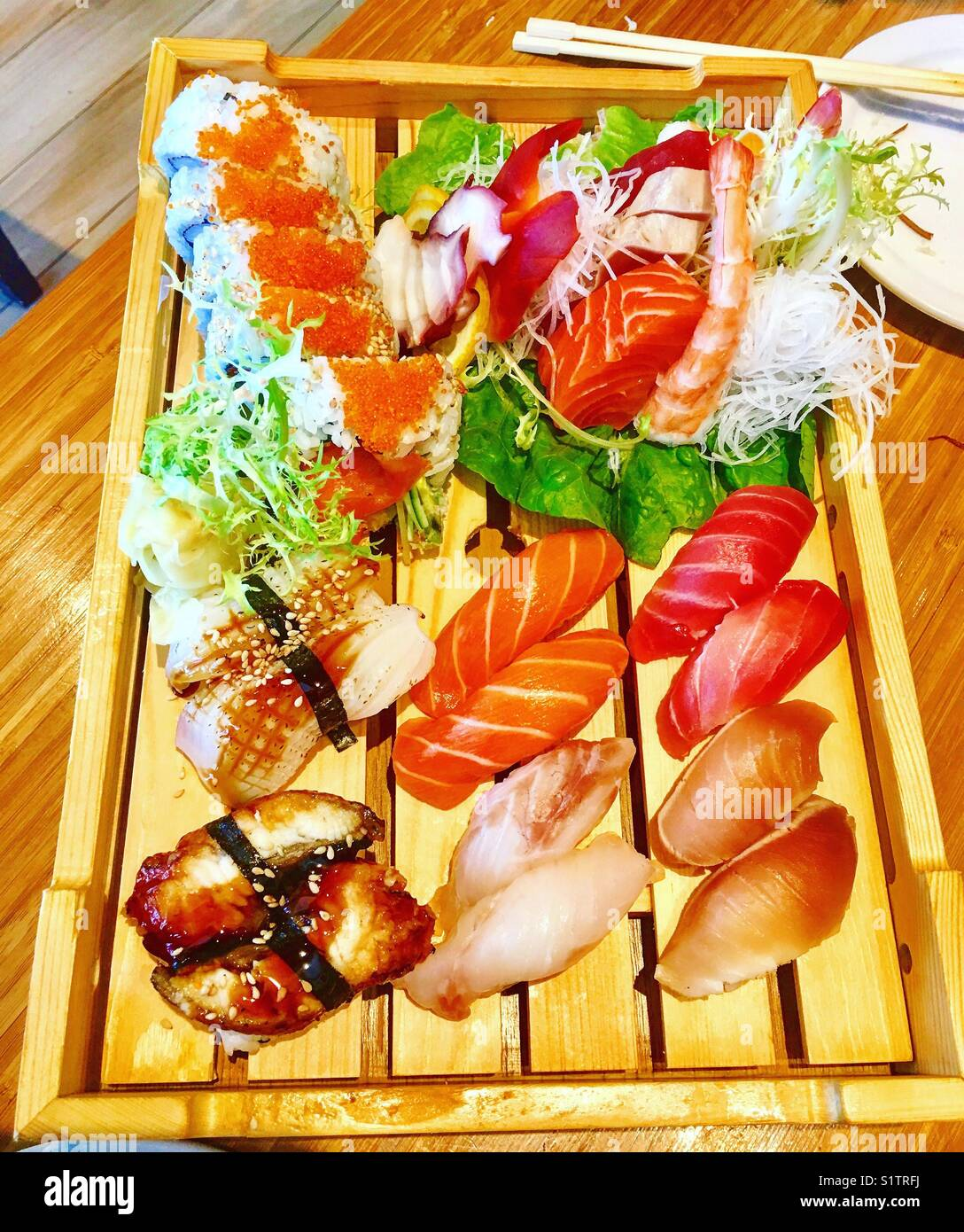 undecided which sushi to eat next with all these tasty goodness right in front of me - Stock Image