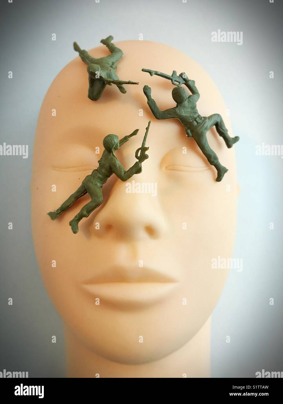 Toy plastic soldiers on plastic human face. - Stock Image