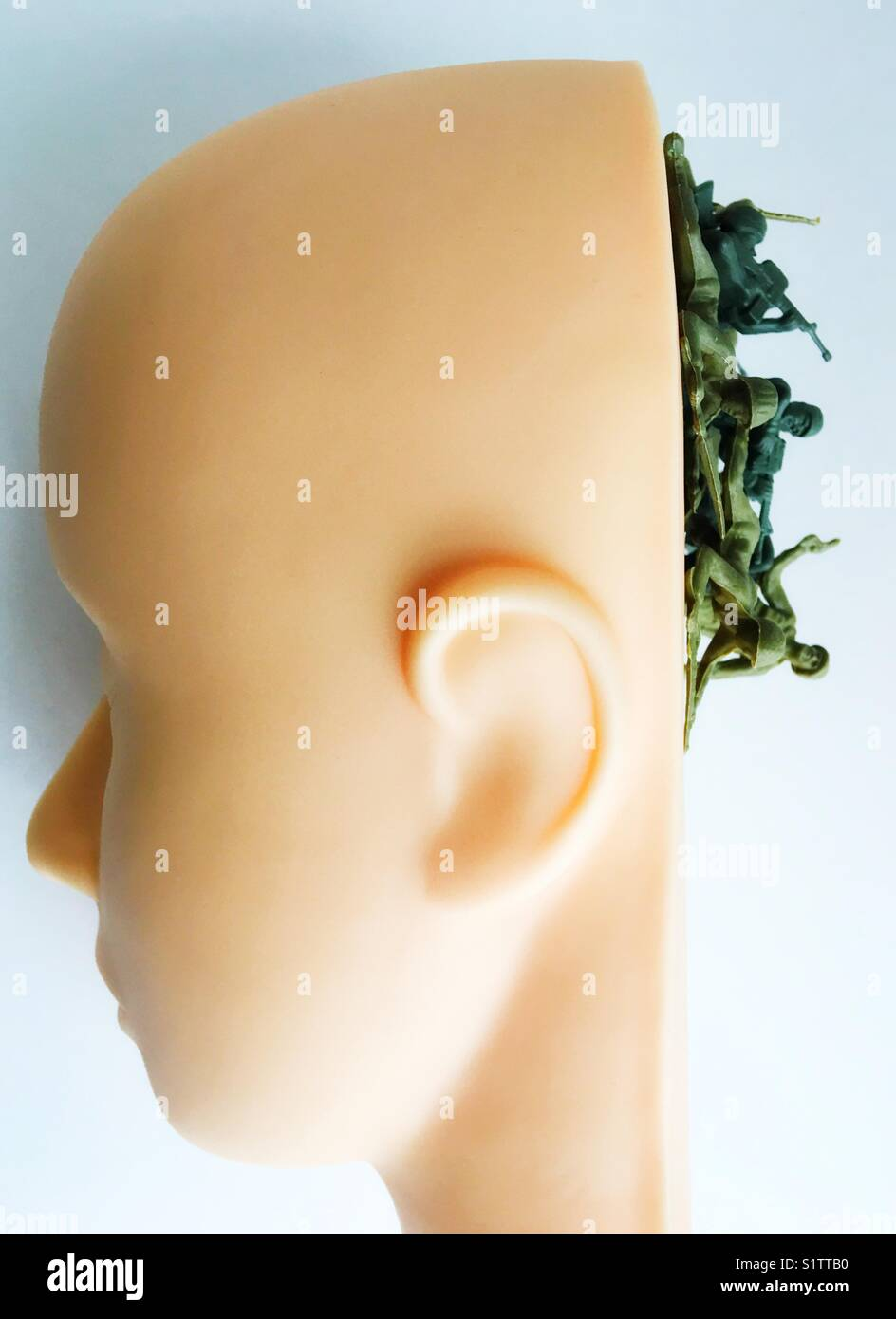 Toy plastic soldiers spilling out of back of mannequin head. - Stock Image