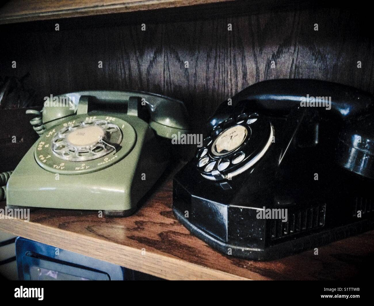 Vintage telephones in wooden bookshelf - Stock Image