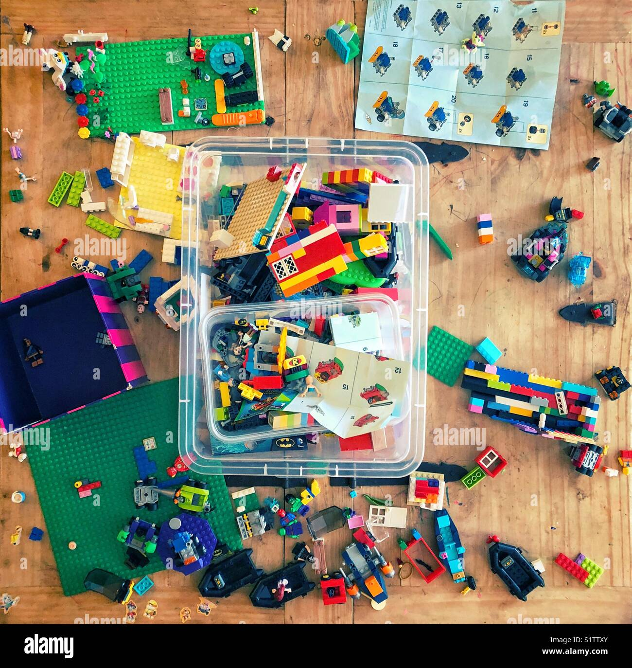 Genuine mess of LEGO blocks made by children after playing for hours on a wooden table - Stock Image