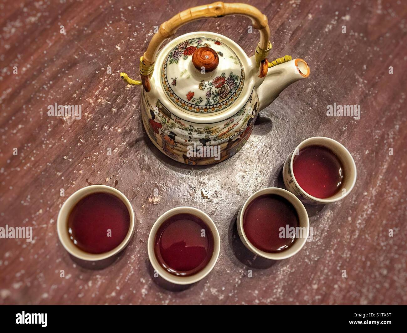 Chinese tea pot with four cups full of tea - Stock Image