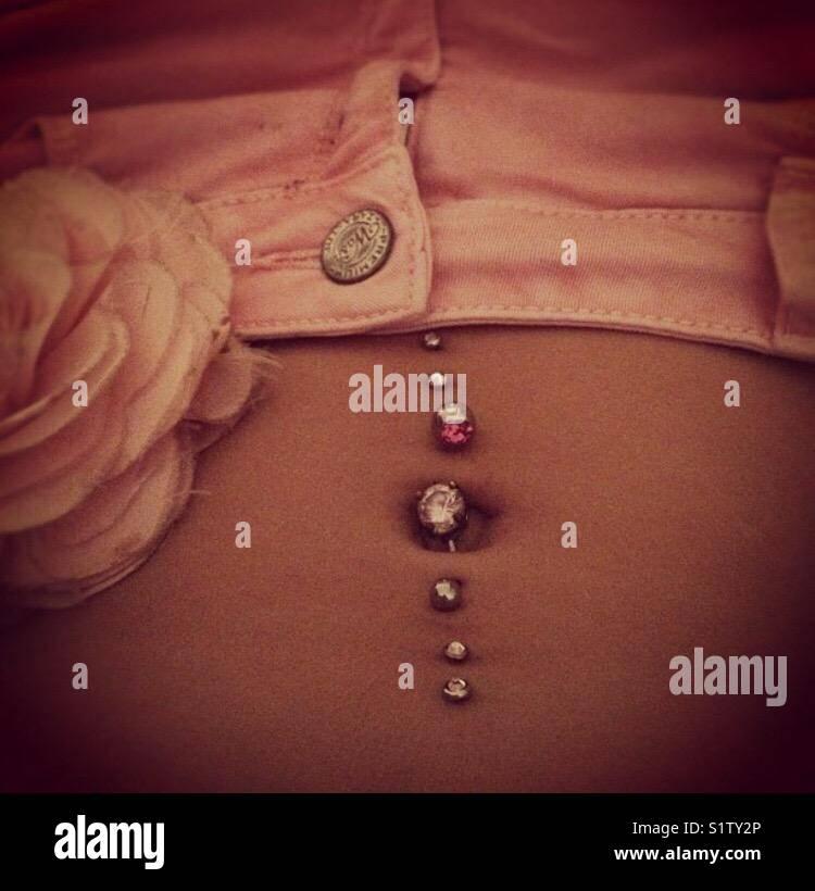 Piercings , Rose & jeans. - Stock Image