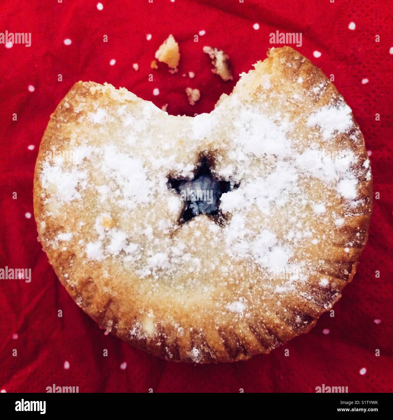 A bite taken out of a Christmas mince pie - Stock Image