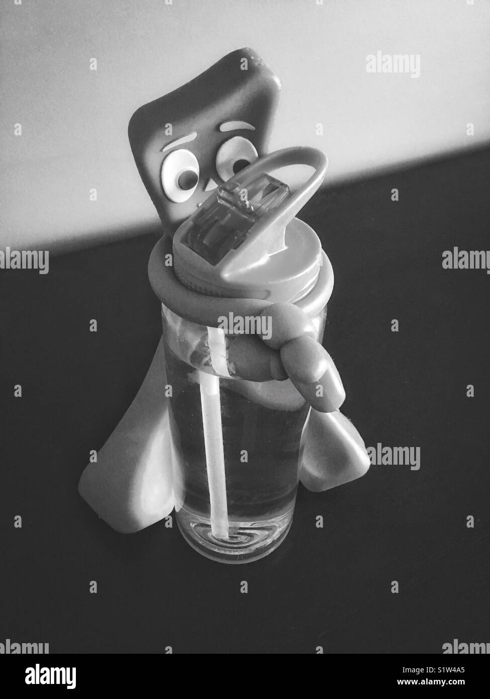 Gumby toy holding a plastic bottle with water, black and white thirst concept - Stock Image