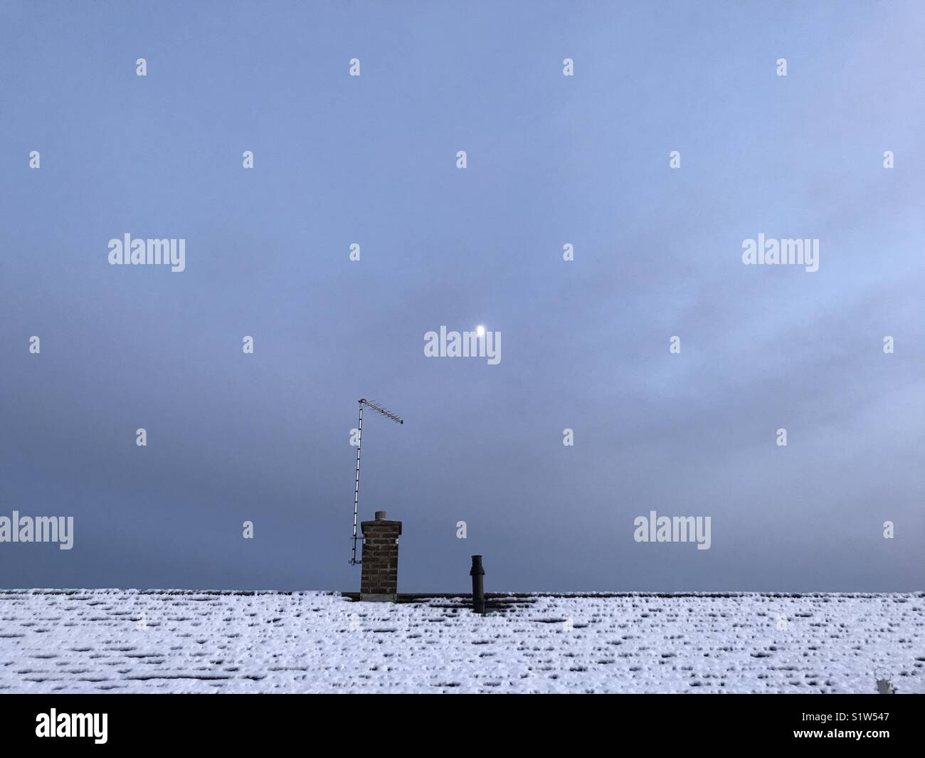 Snowy rooftop at dusk - Stock Image