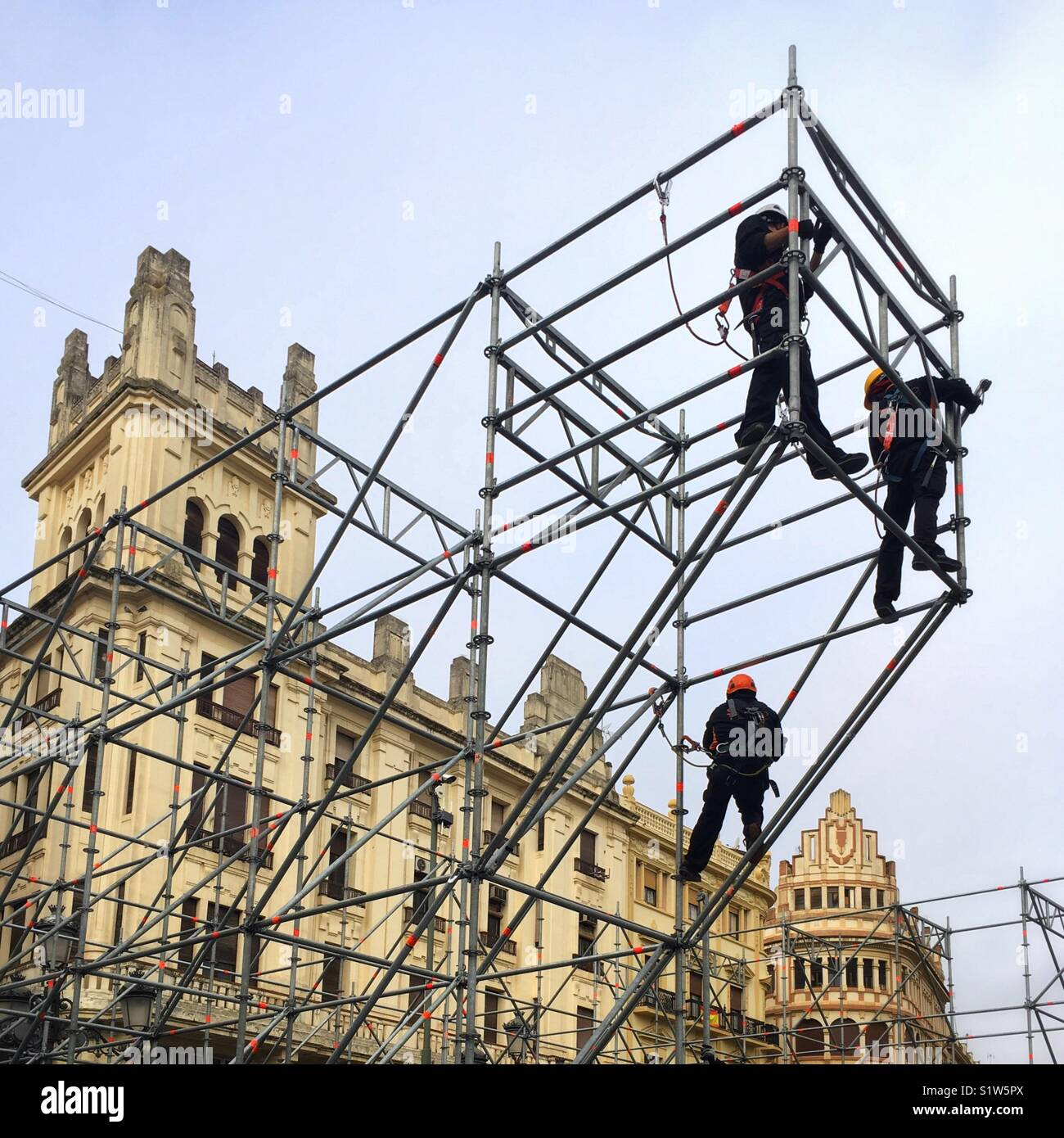 Acrobatic scaffolders build an open air stage in a city square - Stock Image