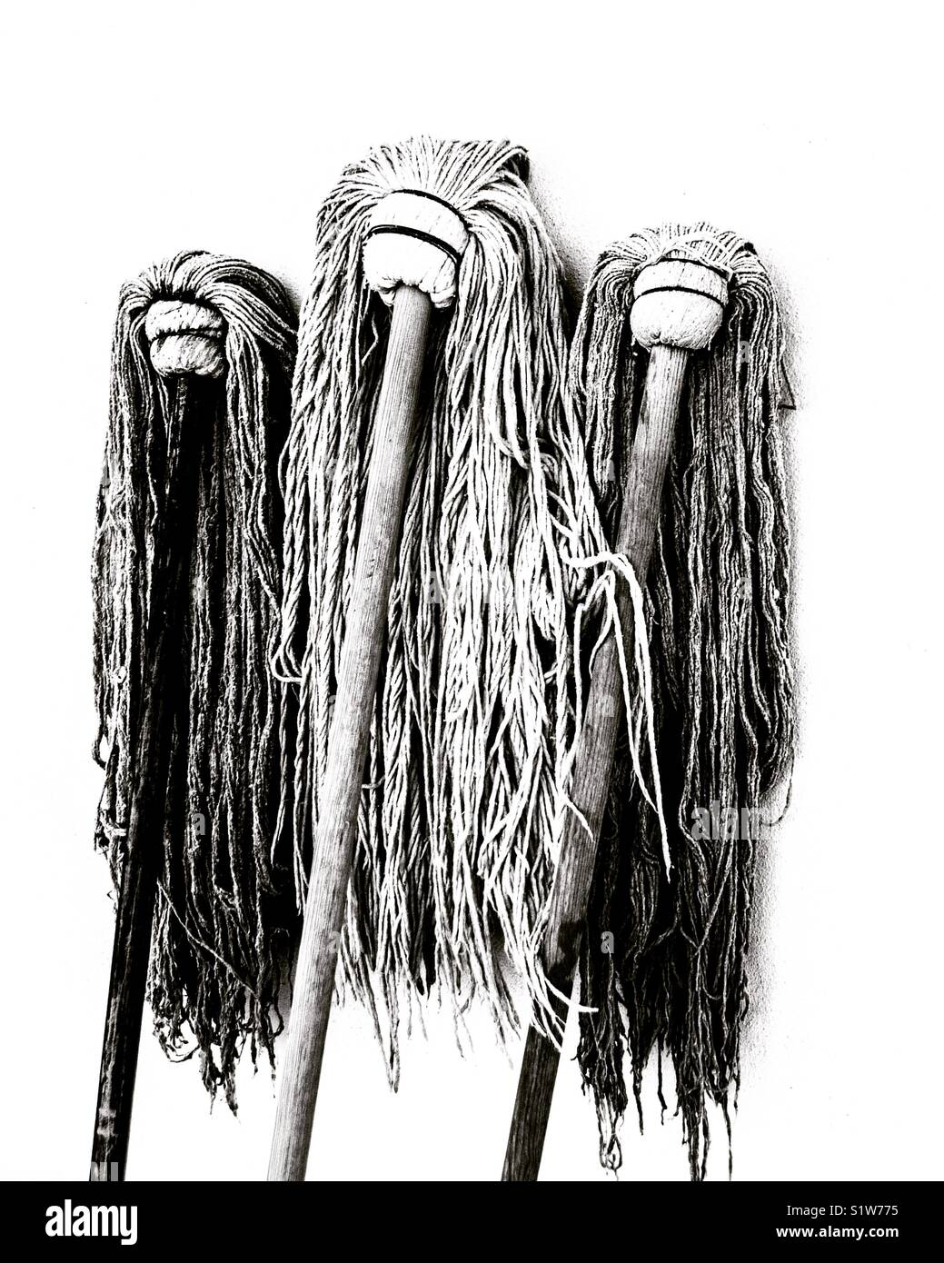 Three mops leaning against a wall. - Stock Image