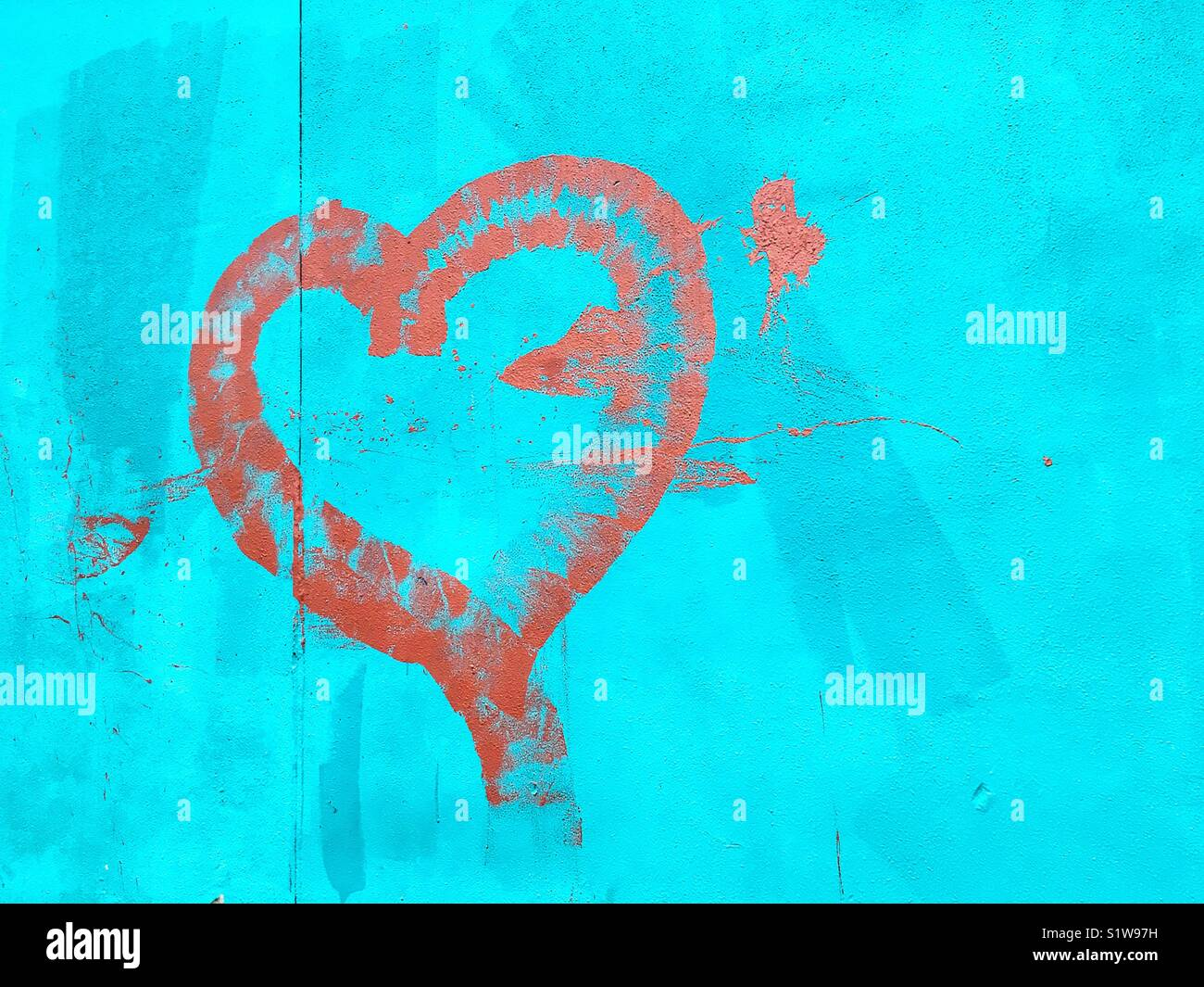 Graffiti depicting a heart painted on a blue wall. - Stock Image