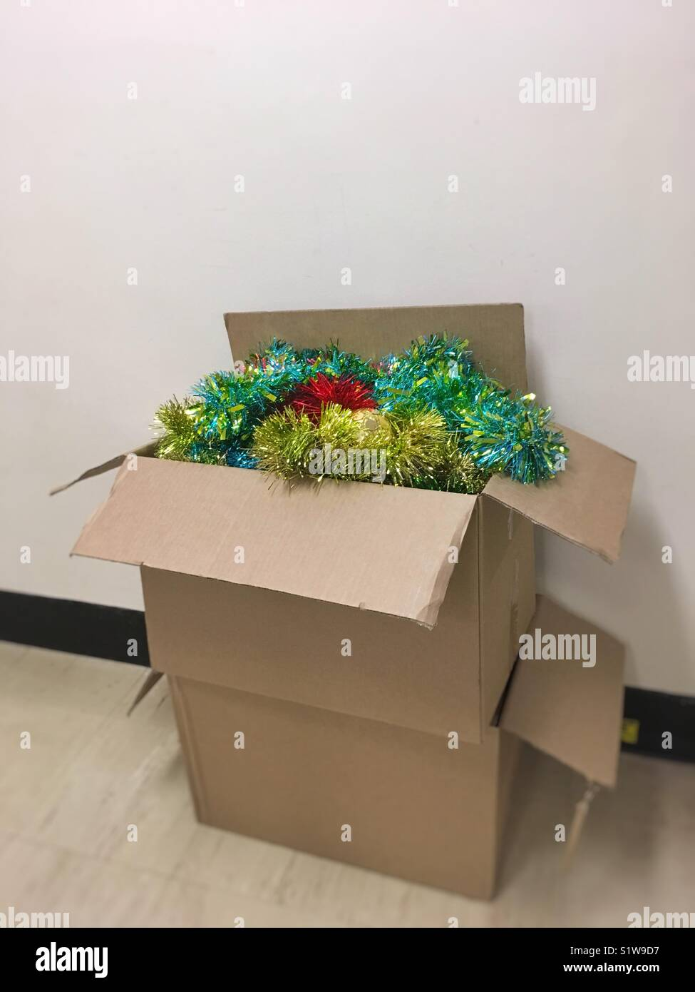 Christmas tinsel being packed away after Christmas. - Stock Image