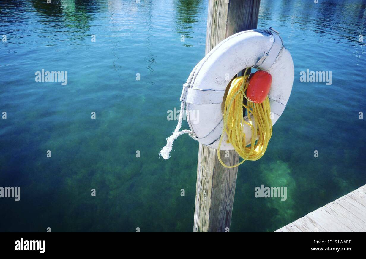 Sunny day on dock with life saver on post - Stock Image