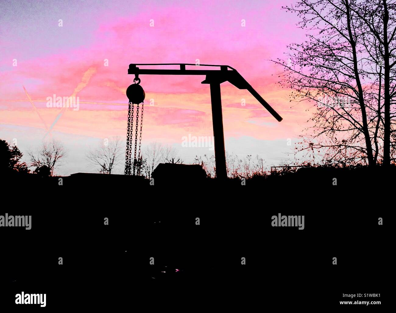 Pastel sunset with farm log lifter in silhouette - Stock Image