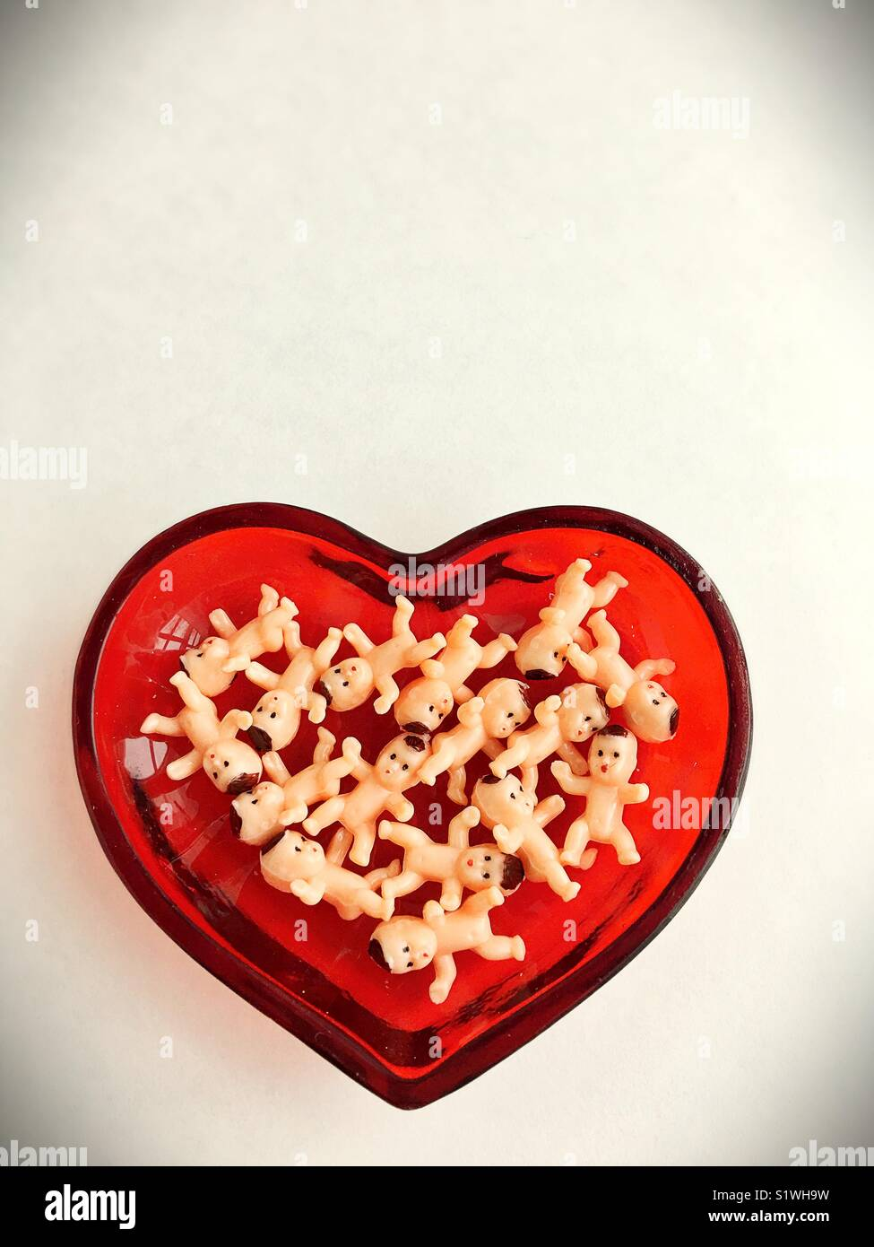 Plastic miniature baby dolls in a heart shaped dish. - Stock Image