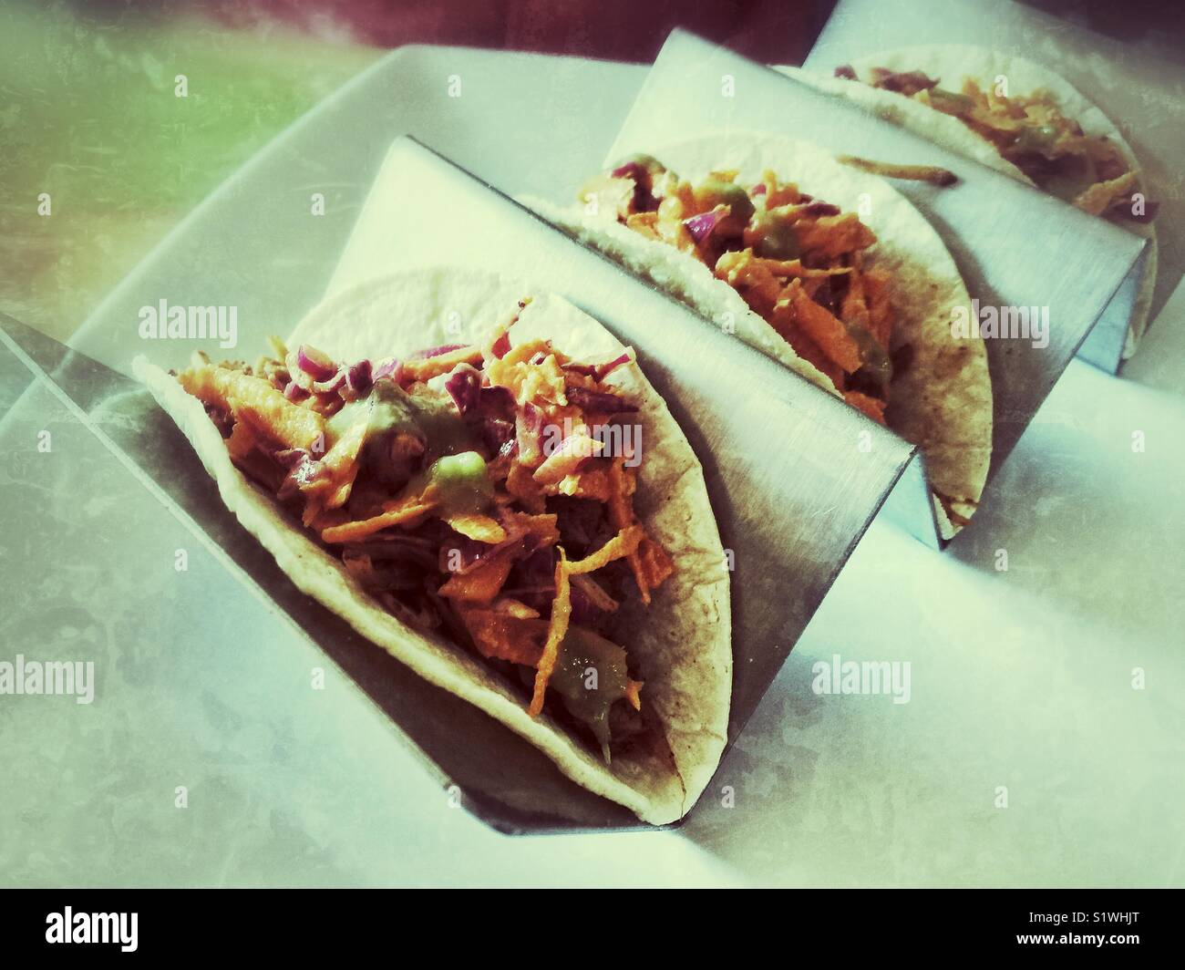 Three tacos on a metal stand in the restaurant Stock Photo