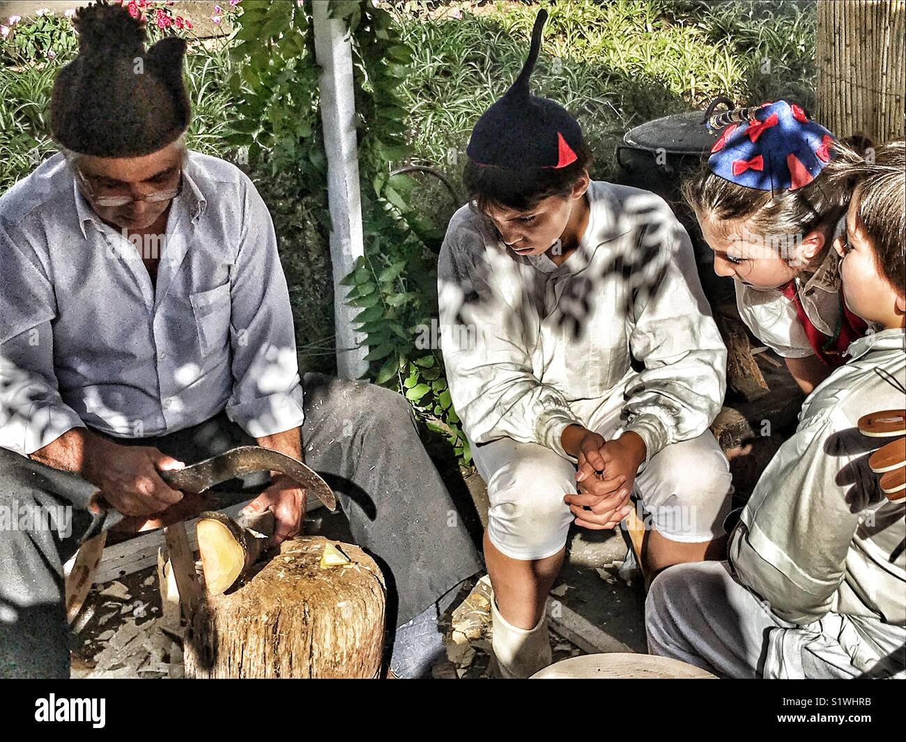 Children watching a craftsman carving wood at the Christmas Market, Funchal, Madeira, Portugal - Stock Image