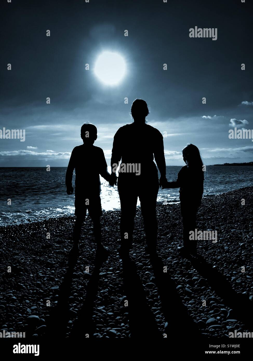 The silhouettes of 3 people - a Mother holds the hands of her 2 children as they all look forward towards a bright Stock Photo