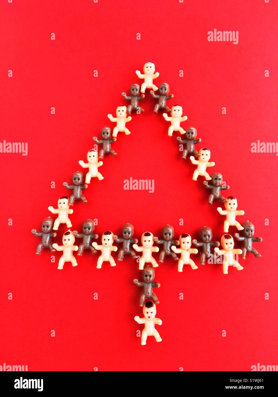 Tiny plastic baby dolls form the shape of a christmas tree. - Stock Image