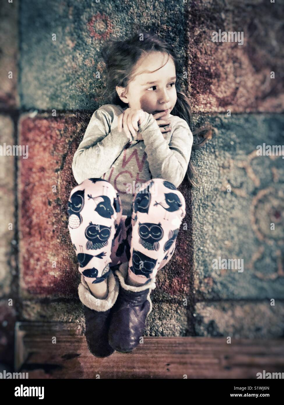 5 year old girl wearing pyjamas curled up in fetal position on carpet floor looking to the side - Stock Image