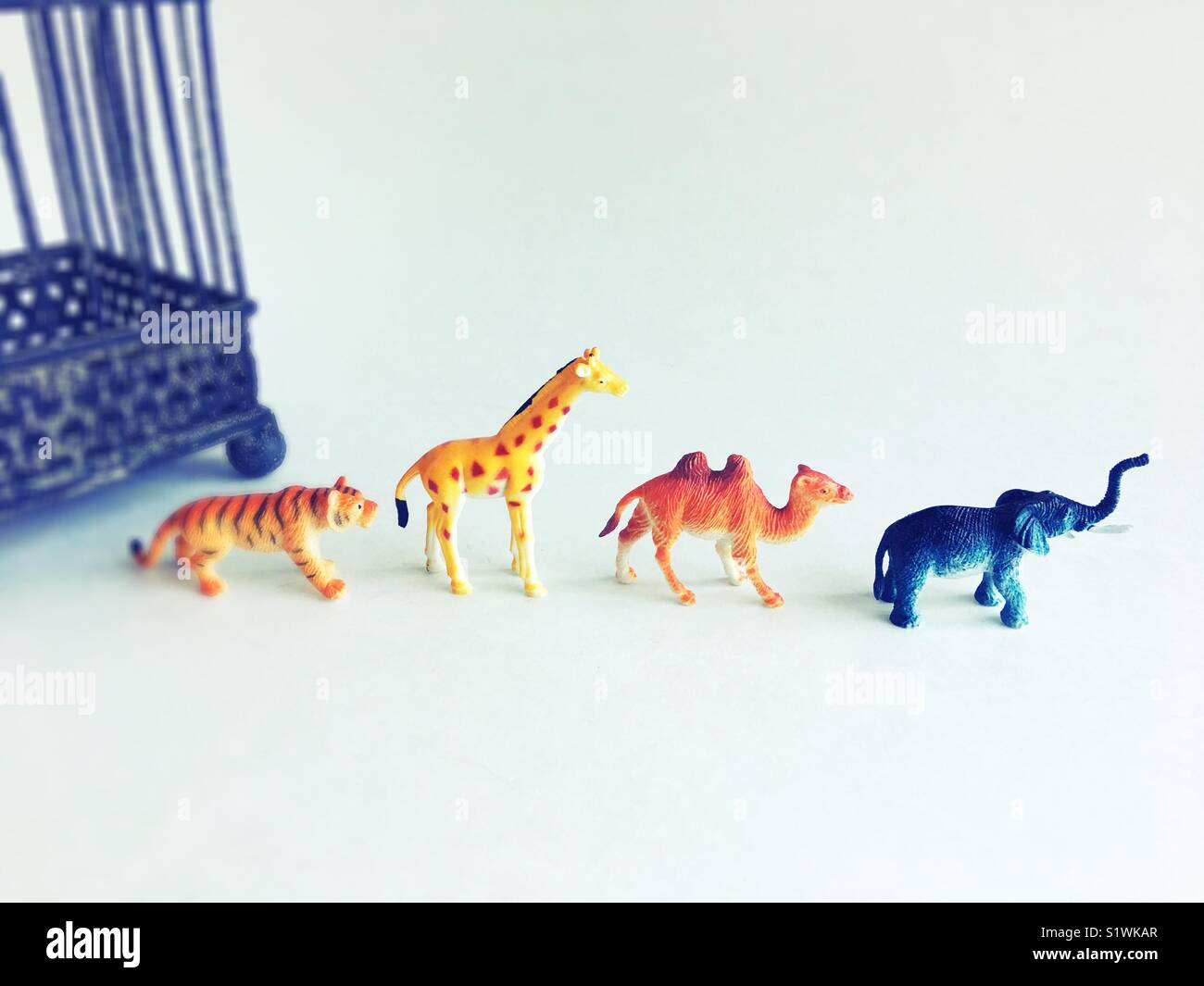 Toy wild animals walking away from a cage. - Stock Image
