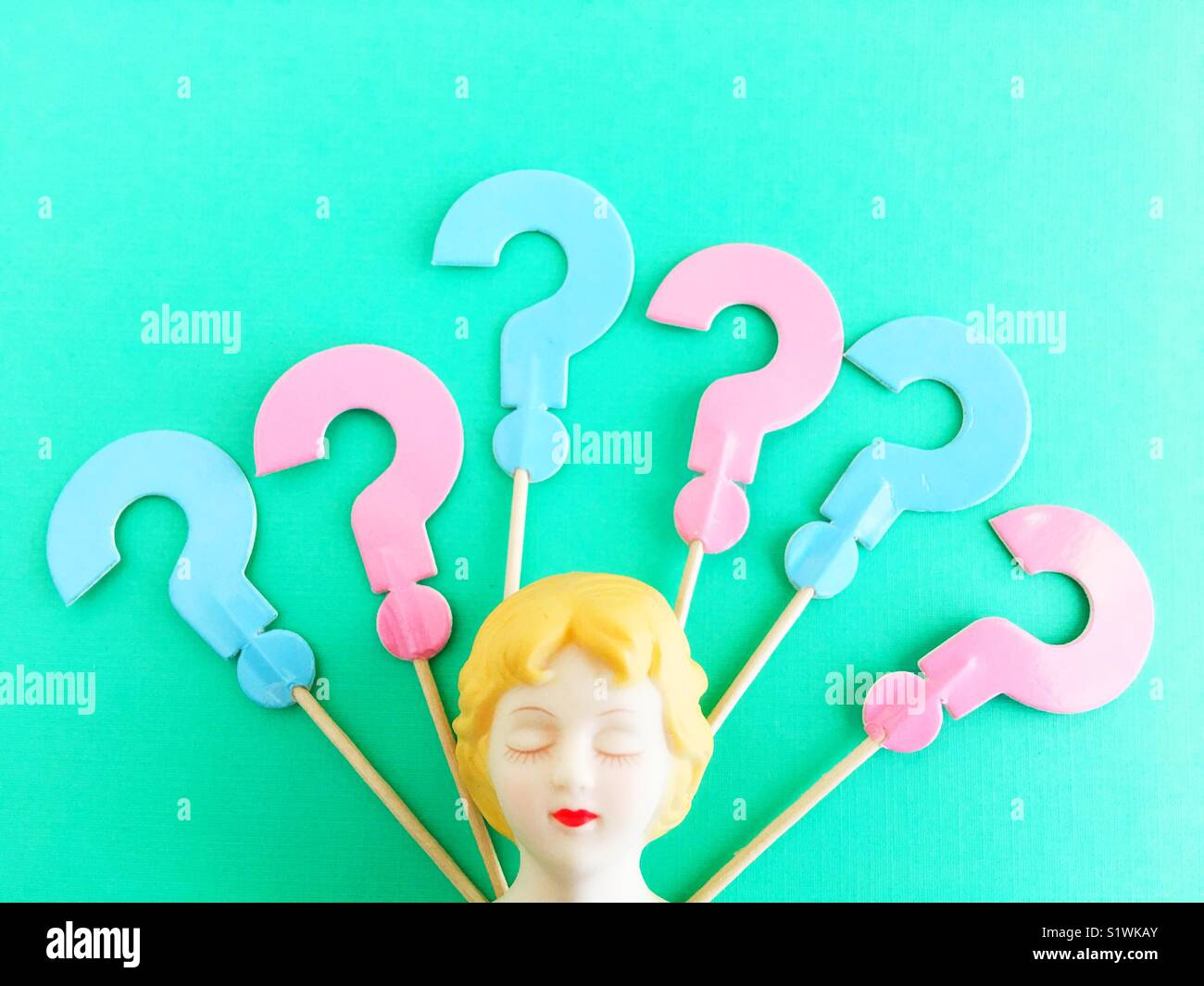 A doll head with eyes closed and question marks. - Stock Image
