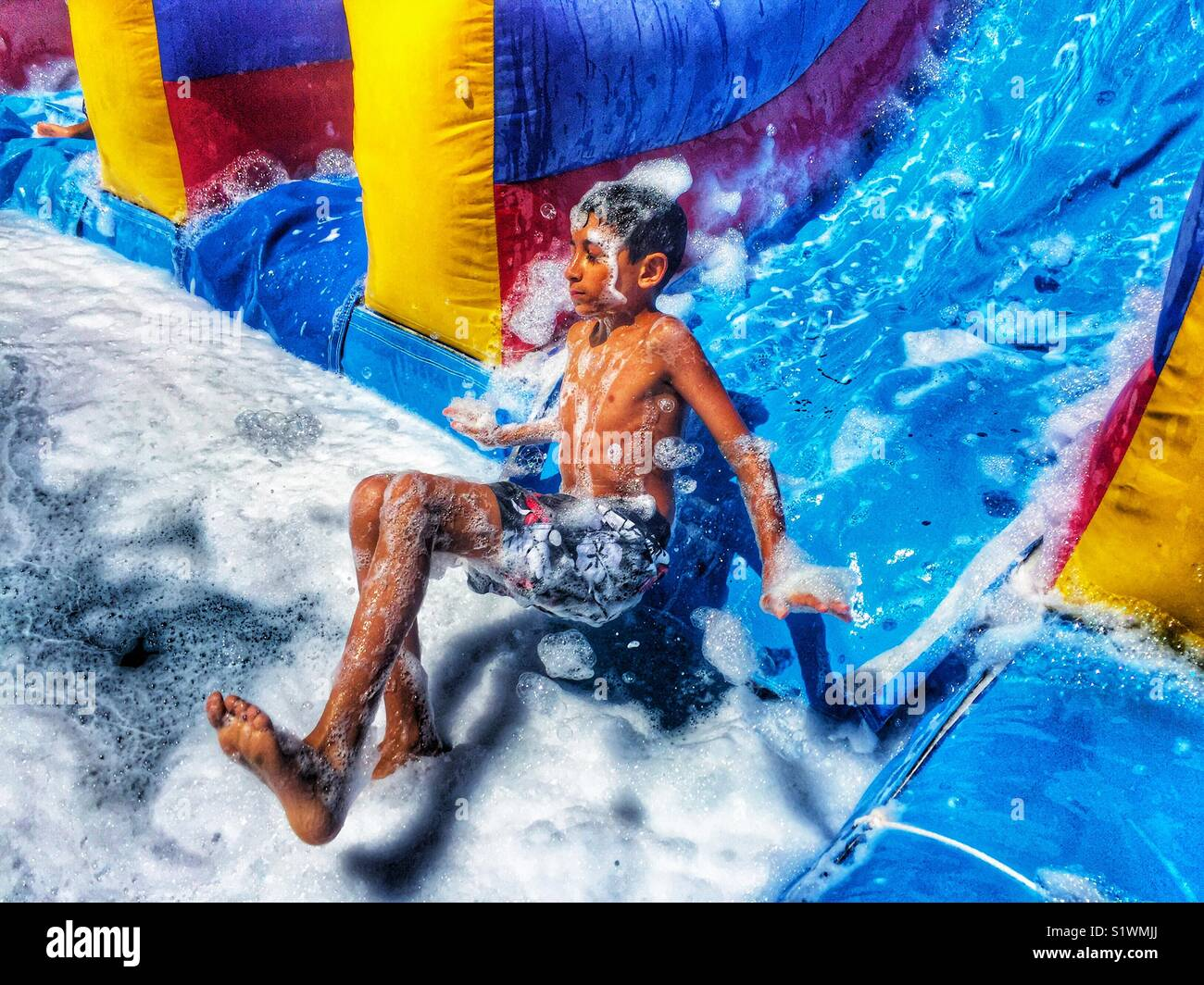 Boy sliding down a water slide with soap - Stock Image