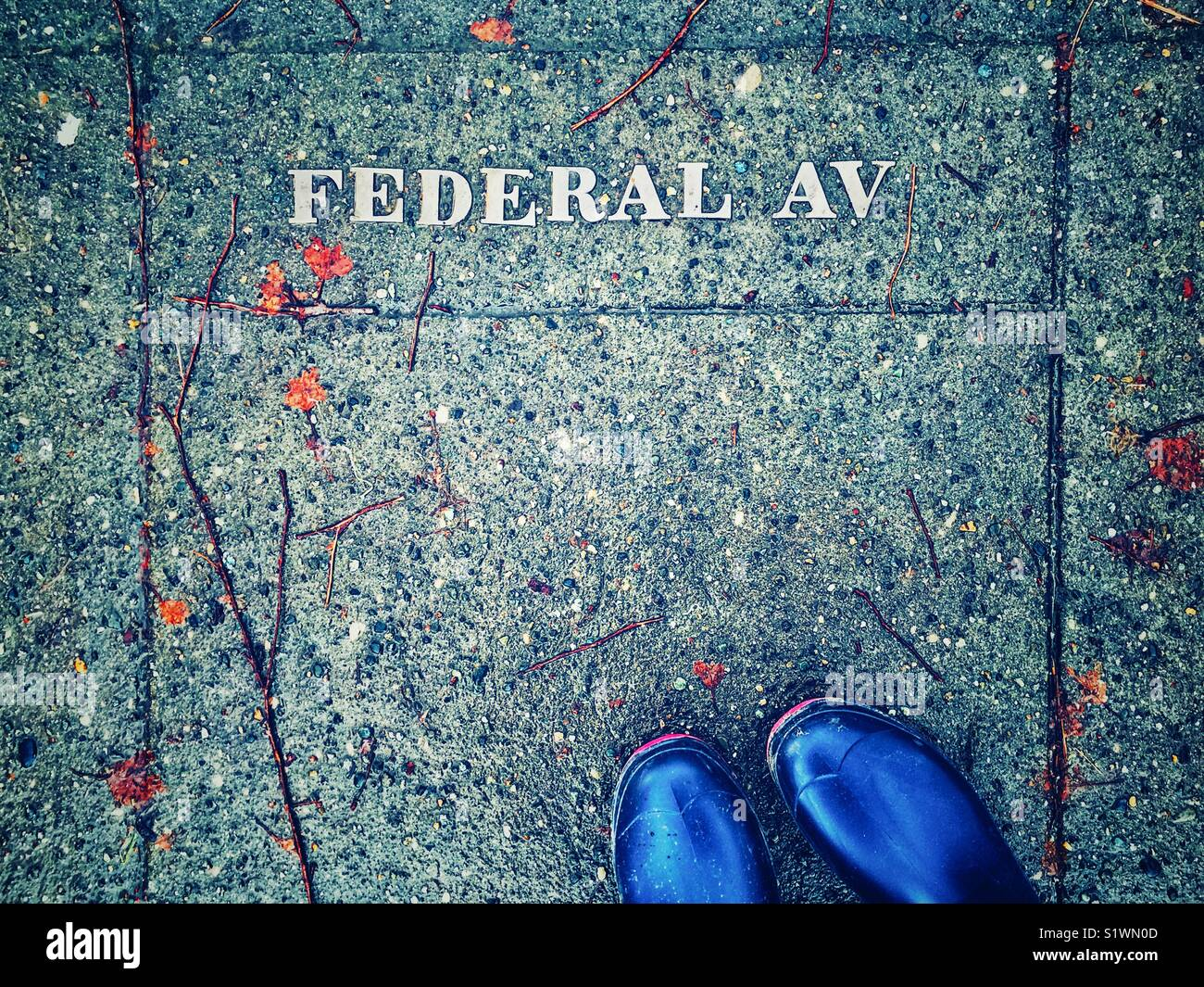 Feet in blue rain boots standing on a sidewalk with Federal Av metal letters in Seattle Washington State - Stock Image