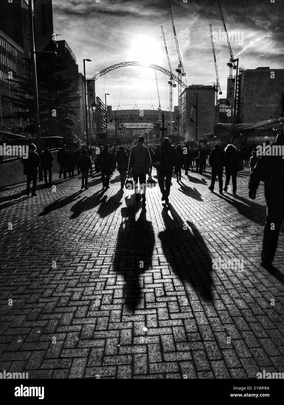 Football supporters walking into the sun towards Wembley Stadium. - Stock Image