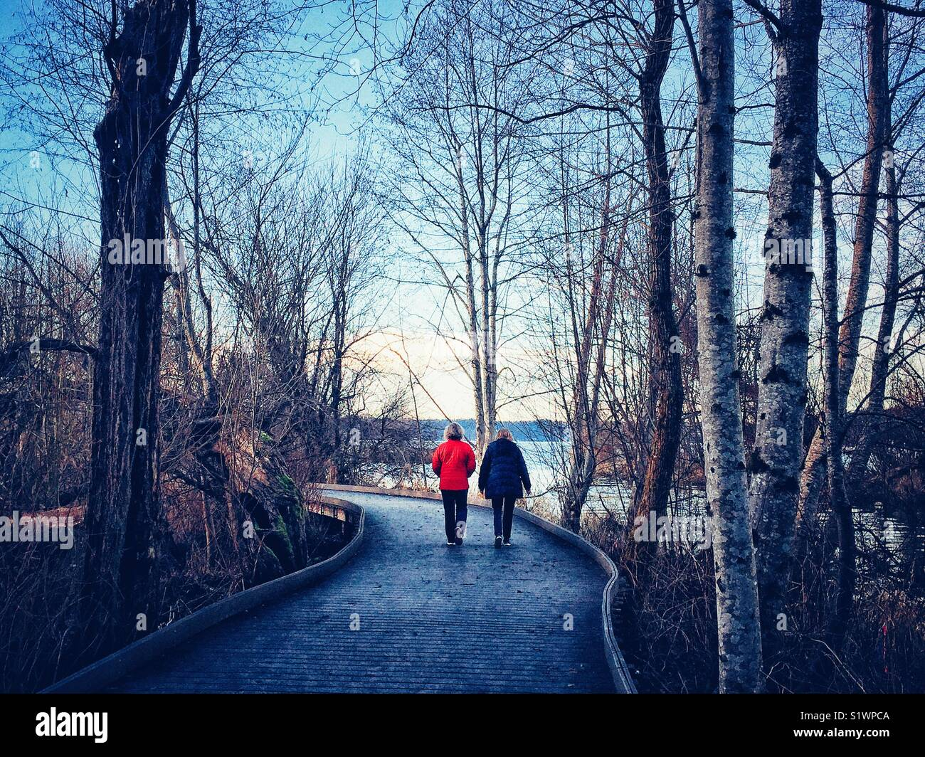 Two women walk on a path to the lake Sammamish, Issaquah, Washington state - Stock Image