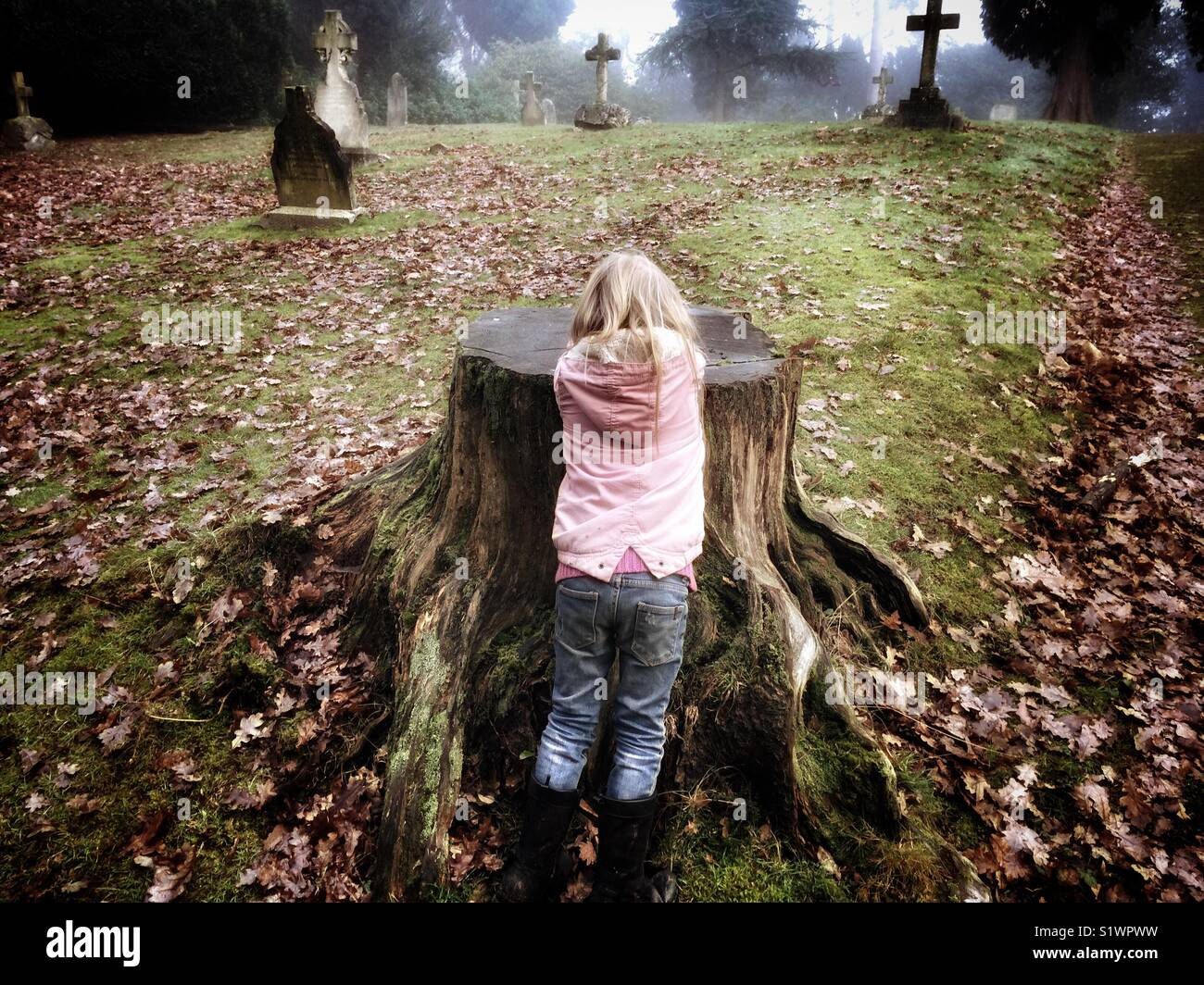 Young child playing hide and seek in a graveyard. Stock Photo