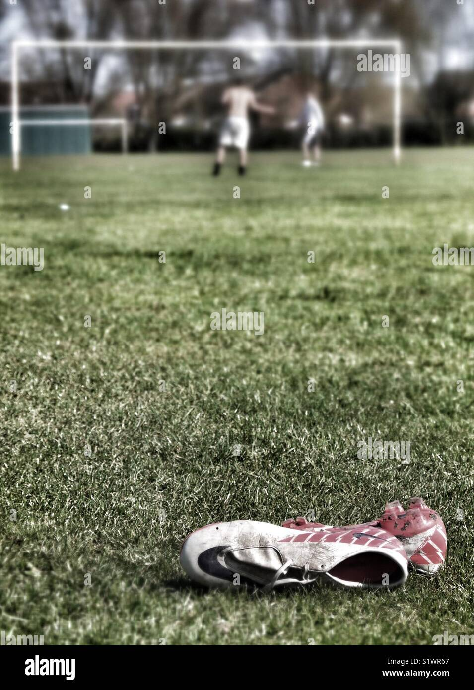Pair of football boots lying in grass. Stock Photo